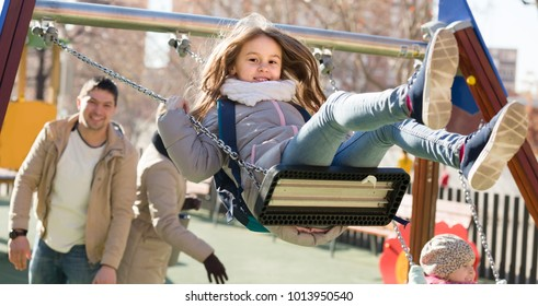 Cheerful american  family with two girls having fun on swings outdoors