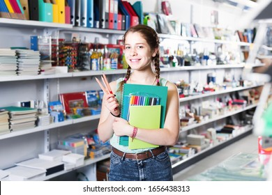 Cheerful american teenager buying different products in stationery shop