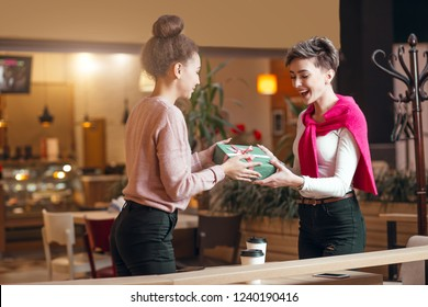 Cheerful amiable girls sit in cafe of shopping center. The happy woman presents a gift for Christmas to her female co-worker . Female togetherness, girlfriends, shopping, holidays celebrating concept