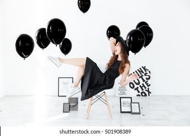 Cheerful amusing young woman sitting and having fun over white background with black balloons and frames