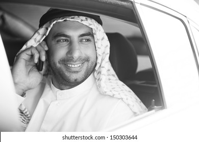 Cheerful Arab businessman. Black and white image of smiling Arab businessman sitting on the back seat of car and talking on the mobile phone
