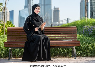 Cheerful arab woman looking in the camera. Muslim Businesswoman in hijab holding tablet .