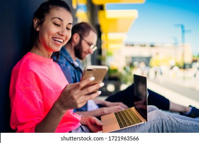 Cheerful Asian blogger sharing media content from smartphone gadget to laptop technology for editing via app, happy hipster freelancer checking received cellphone notification during distance job
