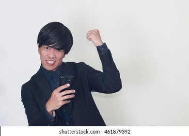 cheerful Asian business man in black suit holding smart phone