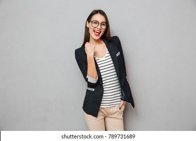 Cheerful asian business woman in eyeglasses rejoices and looking at the camera over gray background