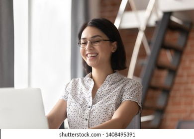 Cheerful asian business woman laughing looking at laptop computer sitting at work desk, happy smiling female korean employee watching funny video online having fun feeling joy at office workplace