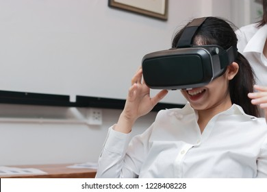 Cheerful Asian business woman wearing virtual reality glasses in office.