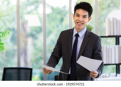 Cheerful Asian businessman in suit smiling and looking at camera while working with documents on blurred background of workplace