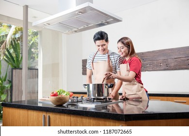 Cheerful asian couple cooking together on the kitchen