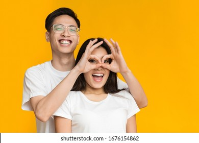Cheerful asian couple in love having fun, guy holding fingers near girlfriend eyes, yellow studio background, both looking at copy space
