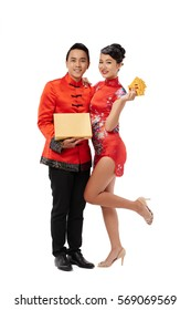 Cheerful Asian couple with present and greeting cards for Tet