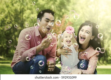 Cheerful Asian family blowing soap bubbles while squatting on the park