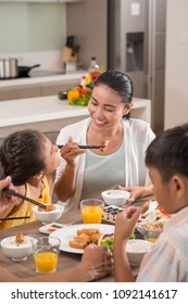 Cheerful Asian family eating sichi and spring rolls at dinner