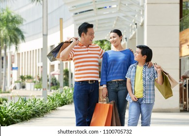 Cheerful Asian family of three holding paper bags in hands and sharing emotions with each other after completion of productive shopping, facade of modern shopping mall on background