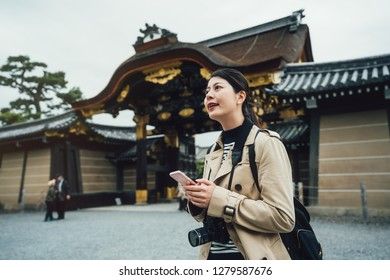 Cheerful asian female traveler holding cellphone searching direction online map app. young girl photographer carrying camera standing near nijo jo gate on sunny day in spring vacation kyoto japan.