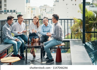 Cheerful Asian friends sitting on terrace with beer bottles on table and relaxing in sunlight on urban background