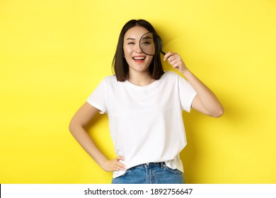 Cheerful asian girl searching for you, looking through magnifying glass and smiling, found something interesting, standing over yellow background