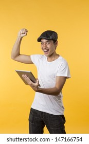 Cheerful Asian man celebrating with his arm up & holding a tablet PC. In front of Yellow background.