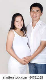 cheerful asian man with his pregnant wife