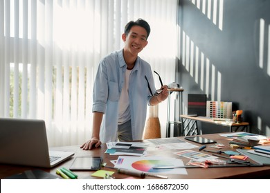 Cheerful asian man holding eyeglasses and smiling at camera while leaning on a table with a lot of creative stuff on it. Young designer in casual wear working in the modern office