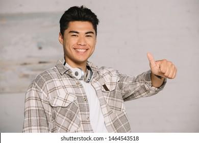 cheerful asian man showing thumb up while smiling at camera at home