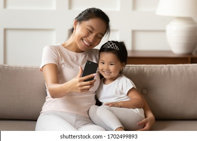 Cheerful Asian mother cuddles little sweet daughter holding smartphone making video call talk to relatives, taking selfie photography for memory, having fun at home use modern application tech concept