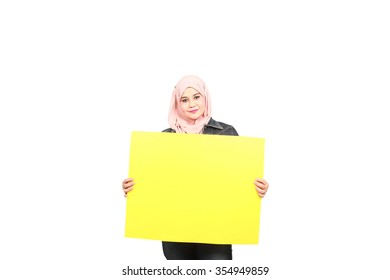 Cheerful asian muslim woman holding empty yellow board on side