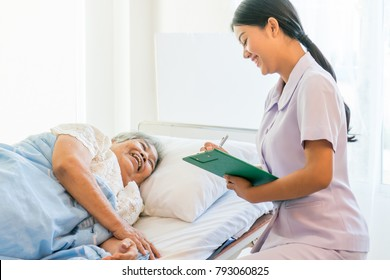 cheerful Asian nurse talking with elderly patient for monitoring and check up. nurse giving consoling to senior and encourage in the hospital.