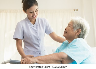 Cheerful asian nurse visiting elderly patient to check up after surgery in hospital for giving physical therapy and encouragement.