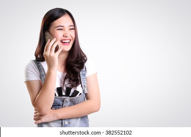Cheerful Asian teenage girl laughing while talking on cellphone, on white background for copy space