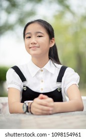 cheerful asian teenager sitting in natural park