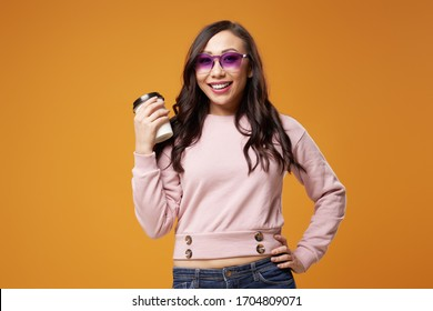 Cheerful asian woman in purple glasses with glass in her hands on orange background