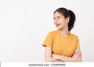 Cheerful Asian woman standing with arms folded and smiling in wearing a yellow shirt, Looking to the side.