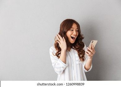 Cheerful asian woman standing isolated over gray background, holding mobile phone, celebrating