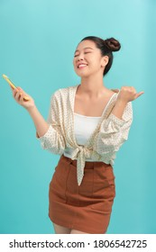 Cheerful asian woman standing isolated over blue background, holding mobile phone, celebrating