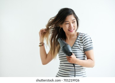 Cheerful Asian young woman blowing out her hair after shower, isolated on white