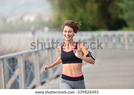 Cheerful athletic girl running outside
