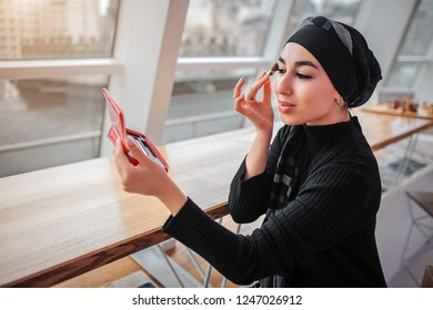 Cheerful and attractive arabian woman doing makeup. She looks in mirror. Model sits inside at tall table near window. Sun is shining.