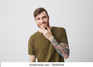 Cheerful attractive bearded caucasian man with blue eyes and tattooed arm looking in camera, smiling with teeth, touching beard with hand.
