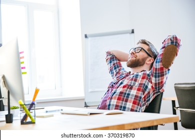 Cheerful attractive bearded young man sitting on workplace with hands behind head and relaxing