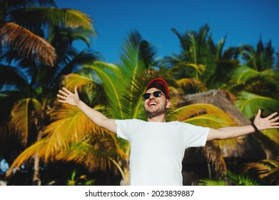 Cheerful attractive boy in white t shirt and sunglasses, gesturing triumph with raised hands against palm trees background