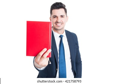 Cheerful attractive businessman giving  or offering a red book and smiling isolated on white studio background
