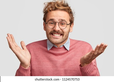 Cheerful attractive European male clasps hands and looks clueless, can`t decide what to choose between two things, has hesitant expression, smiles positively, isolated over white background.