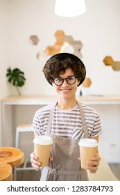 Cheerful attractive hipster barista in hat and glasses standing in modern coffee shop and looking at camera while offering to drink coffee