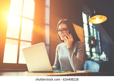 Cheerful attractive hipster girl having phone conversation with service manager of web store talking about sales and money transfer for purchases, beautiful female journalist arranging meeting online