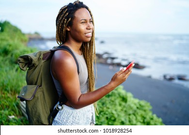 Cheerful attractive tourist with dark skin enjoying tropical scenery of seashore holding smartphone in hands. African american young woman with travel backpack admiring landscape of island during trip