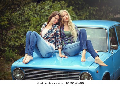 cheerful Attractive two young blonde girl and brunette posing on the hood of an old rusty car, dressed in jeans and shirts on a nature background.