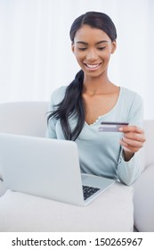 Cheerful attractive woman in bright living room using her laptop to buy online