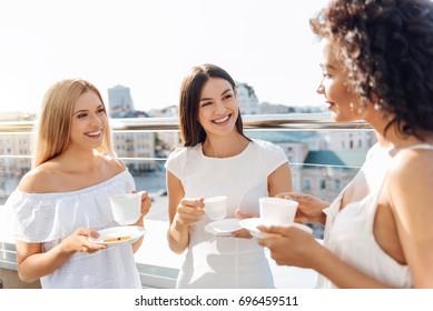 Cheerful attractive women having tea together