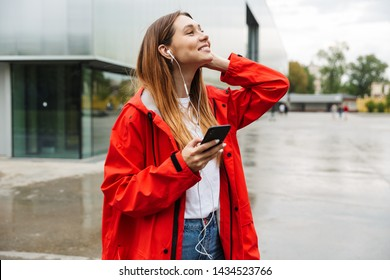 Cheerful attractive young girl wearing raincoat spending lovely time outdoors, listening to music with headphones, holding mobile phone